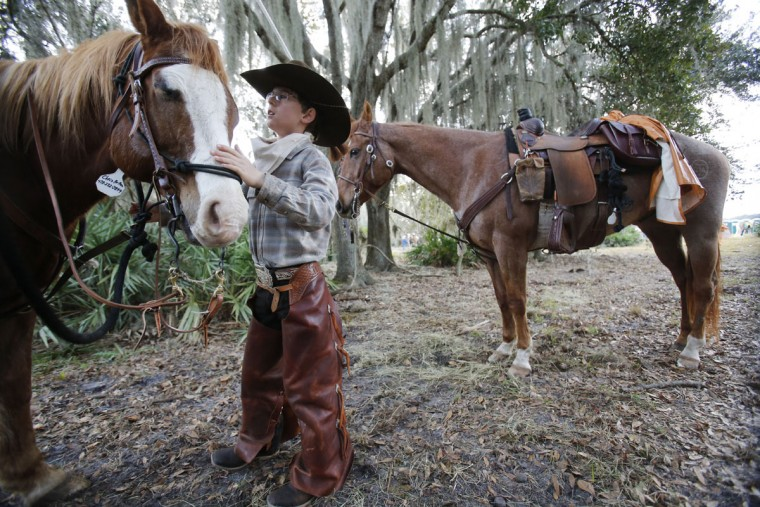 In this, Tuesday, Jan. 26, 2016 photo, Chris Helton, 12, of Sandersville, Ga., prepares his horse Dakota, for the second day of the Great Florida Cattle Drive 2016, in Kenansville, Fla. The purpose of the once-a-decade drive was to draw attention to Floridaís deep cowboy history at a time when the state is known more for Disney World fantasies, South Beach flashiness, Panama City Beach spring break rowdiness and Cape Canaveral rocket launches. (AP Photo/Wilfredo Lee)