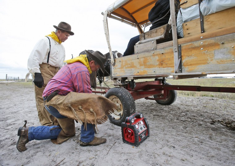 In this, Tuesday, Jan. 26, 2016 photo, Malcolm Jessup, standing, of Spencer, Tenn., looks on as Jeff Parker attempts to air up a flat tire on Jessup's wagon during the Great Florida Cattle Drive 2016, in Kenansville, Fla. There was no AAA tire-repair service for the dozen or so wagons on the ride which stretched through several ranches and state land in Osceola County. The tire on Jessupís covered wagon went flat less than a mile from the campsite on the second day of the cattle drive. (AP Photo/Wilfredo Lee)