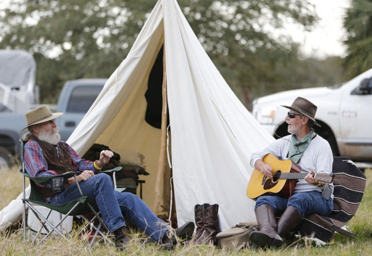 "In this Tuesday, Jan. 26, 2016 photo, storyteller Eric Hoeppner, left, and guitarist Chuck Hardwicke relax at a campsite during the Great Florida Cattle Drive 2016, in Kenansville, Fla. ""We try to remember the way it used to be and draw attention that the cattle industry was the first industry in America,"" says Doyle Conner Jr., who is chairman of the cattle drive. (AP Photo/Wilfredo Lee)"