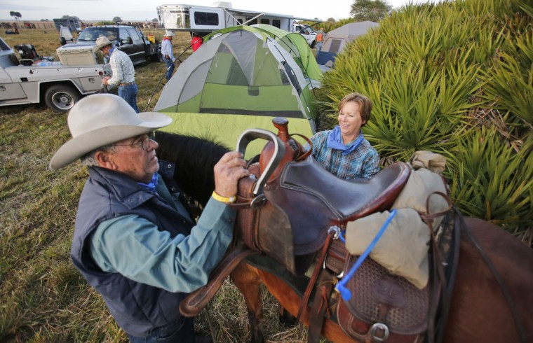 In this Tuesday, Jan. 26, 2016 photo, Ellison Hardee and his daughter Robin, of Chiefland, Fla., saddle their horse, Dilly, during the second day of the Great Florida Cattle Drive 2016, in Kenansville, Fla. More than 400 participants took part in the once-in-a-decade cattle drive through the heart of Florida. (AP Photo/Wilfredo Lee)