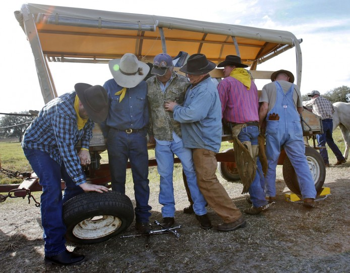 In this Tuesday, Jan. 26, 2016 photo, cowboys lift up a covered wagon to remove a flat tire on Malcolm Jessup's wagon during the Great Florida Cattle Drive 2016, in Kenansville, Fla. The tire on Jessup's covered wagon went flat less than a mile from the campsite on the second day of the cattle drive. (AP Photo/Wilfredo Lee)