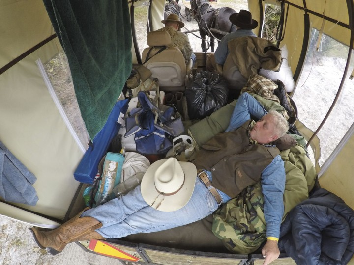 In this Tuesday, Jan. 26, 2016 photo, Steve Pyle of DeLand, Fla., a veteran attending with the Wounded Warrior Project, relaxes in the back of a covered wagon as he waits for the start of the second day of the Great Florida Cattle Drive 2016, in Kenansville, Fla. (AP Photo/Wilfredo Lee)