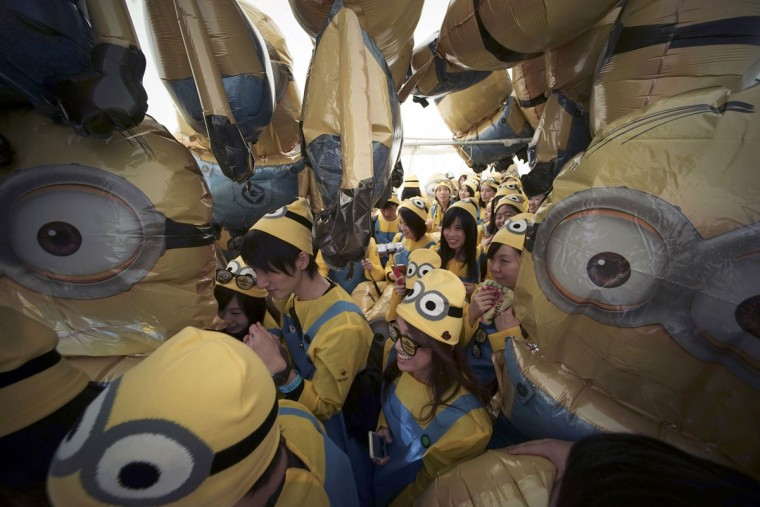 "Participants dressed as ""minions"" walk through the balloon depicting minions during the Minions Run in Tokyo, Saturday, Feb. 13, 2016. Some 10,000 runners enjoyed one kilometer run for the charities of children. (AP Photo/Eugene Hoshiko)"