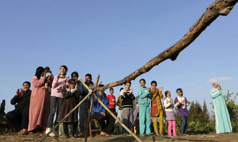 In this Friday, Feb. 5, 2016 picture, children applaud Ahmed Ayman, 14, and his donkey after they jumped over a barrier in the Nile Delta village of Al-Arid about 150 kilometers north of Cairo, Egypt. A cousin has posted pictures of the feat online, which have been spread through social media.(AP Photo/Amr Nabil)