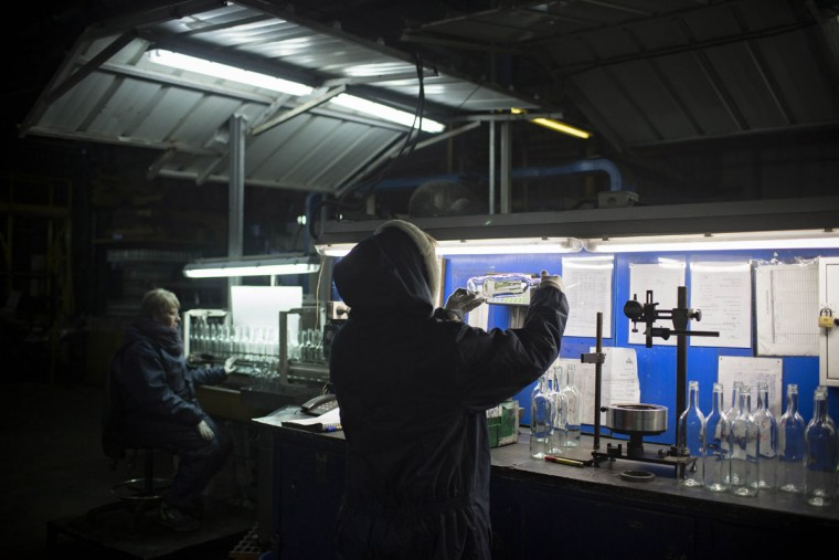 In this Wednesday, Jan. 27, 2016 photo, an employee checks the quality of glass bottles on the production line at Phoenicia Glass Works Ltd. factory in the southern Israeli town of Yeruham. Phoenicia Glass Works, Israelís only glass container factory, produces one million containers a day. Some 300,000 bottles a day come out with defects, and the factory grinds them into shards and piles them in a desert lot to be melted into new bottles. The factory is in the middle of the desert, and works round the clock, every day of the year. (AP Photo/Oded Balilty)