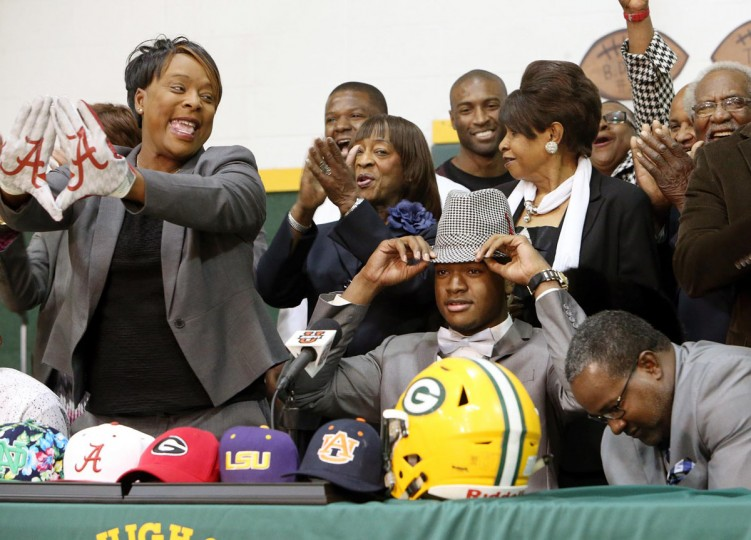Gordo High School football player Ben Davis, seated beside his parents, Faye and Wayne, dons a houndstooth hat after committing to attend Alabama during a national signing day Program at Gordo High School, Wednesday, Feb. 3, 2016, in Tuscaloosa Ala. (Michelle Lepianka Carter/The Tuscaloosa News via AP)