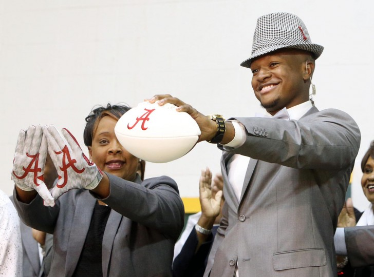 Gordo High School football player Ben Davis, with his mother Faye, left, holds up a football after committing to attend Alabama during a national signing day Program at Gordo High School, Wednesday, Feb. 3, 2016, in Tuscaloosa Ala. (Michelle Lepianka Carter/The Tuscaloosa News via AP)