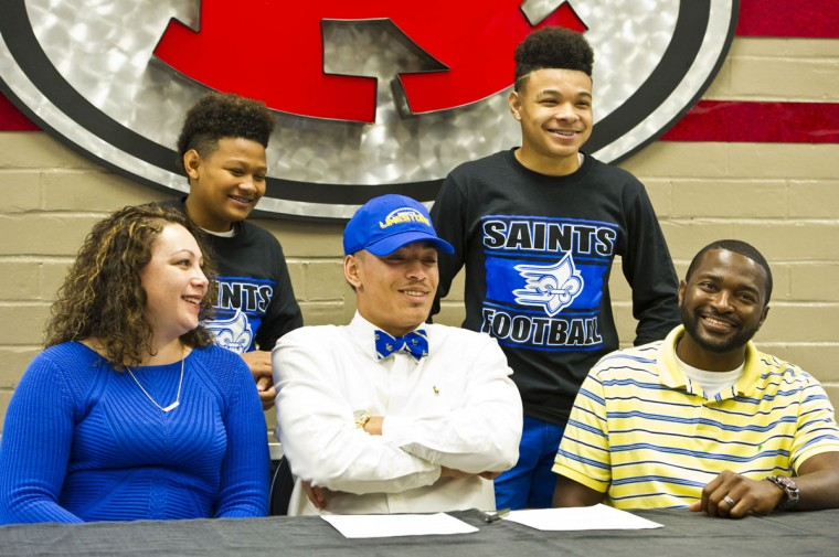 Warner Robins football standout Ivan Corbin are flanked by his parents Amber and Desmond Cobbs, after he signed a letter of intent to attend Limestone College in South Carolina during national signing day, Wednesday, Feb. 3, 2016, in Warner Robbins, Ga. (Woody Marshall/The Macon Telegraph via AP)