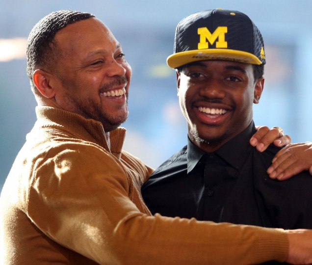 Thomas Wilcher,l eft, head coach at Cass Tech High School, embraces football player Lavert Hill, who signed a letter of intent attend the University of Michigan, during national signing day, Wednesday, Feb. 3, 2016, at the Horatio Williams Foundation headquarters in Detroit. (Kirthmon F. Dozier/Detroit Free Press via AP)