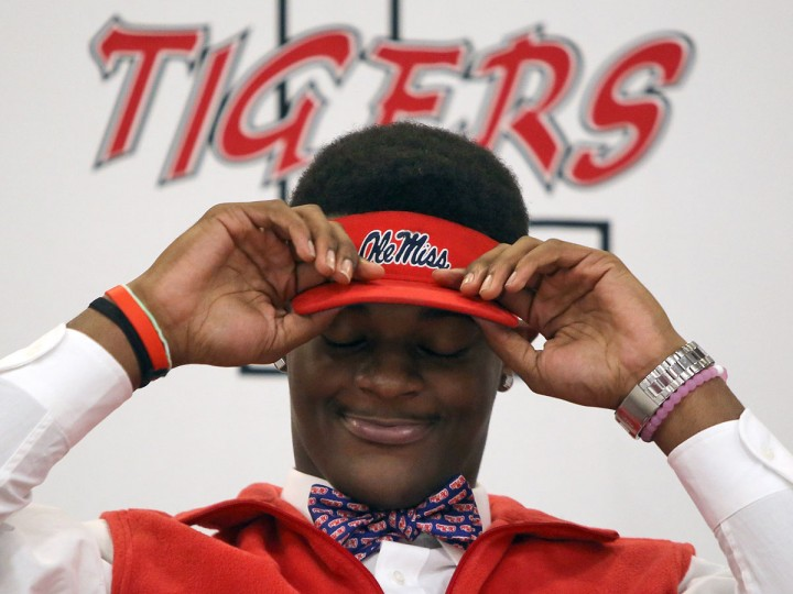 Football player Tariqious Tisdale puts on an Ole Miss visor after he signed his letter of intent to attend Mississippi during national signing day at Lexington High School, Wednesday, Feb. 3, 2016, in Lexington, Tenn. (C.B. Schmelter/The Jackson Sun via AP)