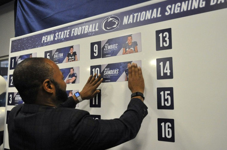 Penn State football assistant head coach Terry Smith places a card on the board with recruit Miles Sanders name on it during national signing day, Wednesday, Feb. 3, 2016, in State College, Pa. (Nabil K. Mark/Centre Daily Times via AP)