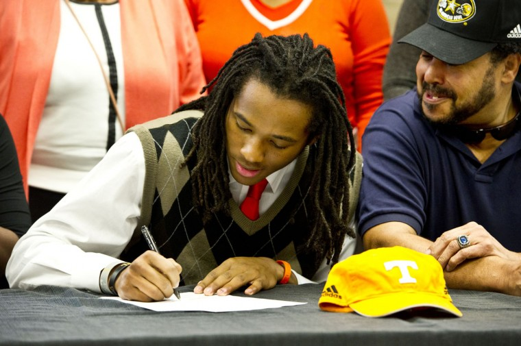 Warner Robins football standout Marquez Callaway signs a letter of intent to attend Tennessee as his father, DuVaal Callaway, right, watches during national signing day, Wednesday, Feb. 3, 2016, in Warner Robbins, Ga. (Woody Marshall/The Macon Telegraph via AP)