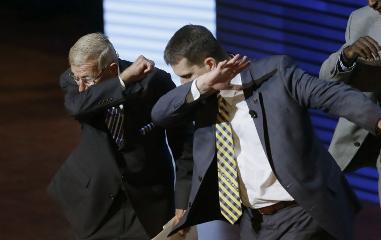 Former coach Lou Holtz, left, and University of Michigan football coach Jim Harbaugh perform a dab during the Signing With the Stars spectacle, Wednesday, Feb. 3, 2016 in Ann Arbor, Mich. Guests and superstars appeared on stage to welcome the University of Michigan's new recruits on National Signing Day. (AP Photo/Carlos Osorio)