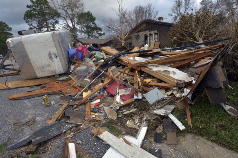 Debris scatters property in the Northpointe neighborhood in Pensacola, Fla., Wednesday Feb. 24, 2016, after a powerful storm affected the area. Florida Gov. Rick Scott said an apparent tornado significantly damaged many homes and apartments in the Pensacola area. (Tony Giberspon/Pensacola News Journal via AP)