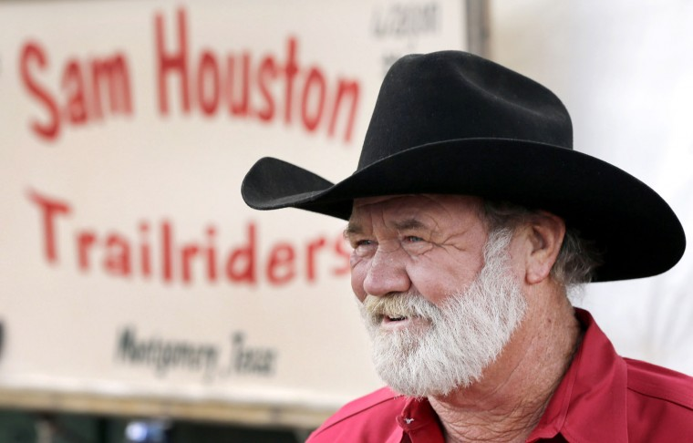 Sam Houston Trail Ride trail boss Earl Blackmon talks with fellow riders at a campsite in Tomball, Texas, Tuesday, Feb. 23, 2016. Blackmon is leading more than 100 riders along the trail as they make their way to Houston for the Houston Livestock Show and Rodeo parade on Saturday. (AP Photo/David J. Phillip)
