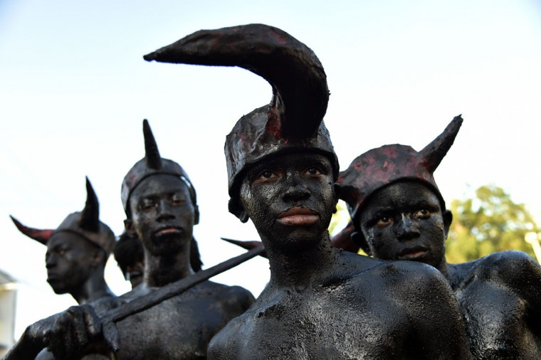 Revelers, their bodies painted with a mixture of cane sugar syrup and coal depicting the devil, perform during the 2016 National Carnival Parade on February 10, 2016 in Port-au-Prince, Haiti. (HECTOR RETAMAL/AFP/Getty Images)