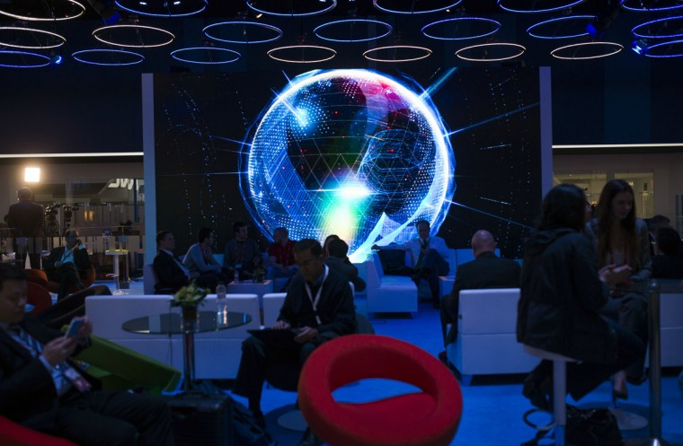 People gather at the lounge area of Intel stand during the Mobile World Congress Wireless show in Barcelona, Spain, Wednesday, Feb. 24, 2016. (AP Photo/Francisco Seco)