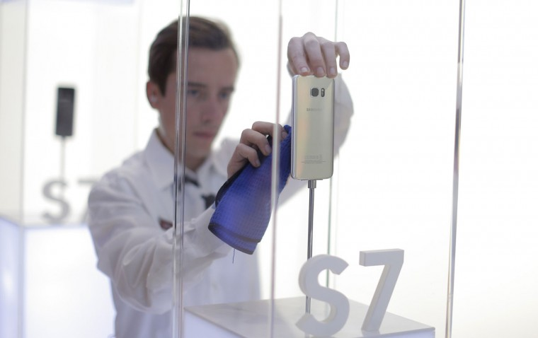 A staff member cleans a Samsung Galasy S7 during the Mobile World Congress wireless show in Barcelona, Spain, Wednesday, Feb. 24, 2016. (AP Photo/Manu Fernandez)