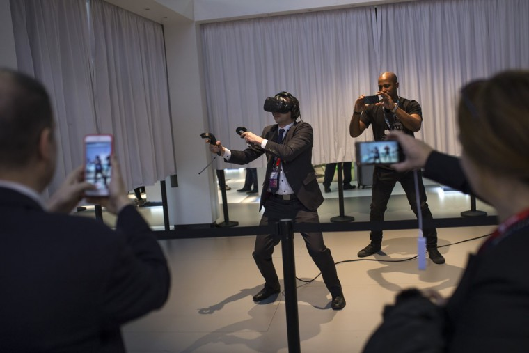 A man uses virtual reality gadgets to play a game during the Mobile World Congress Wireless show in Barcelona, Spain, Wednesday, Feb. 24, 2016. (AP Photo/Francisco Seco)