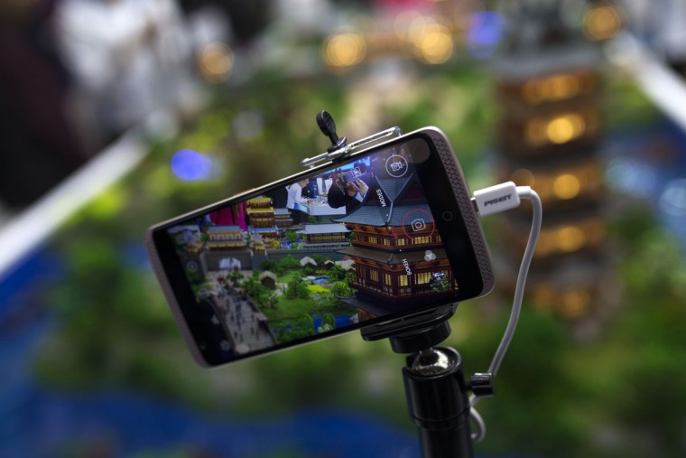 A man, seen on the screen of a smart phone, takes photographs of a miniature city set at the Chinese ZTE stand during the Mobile World Congress Wireless show in Barcelona, Spain, Tuesday, Feb. 23, 2016. (AP Photo/Francisco Seco)