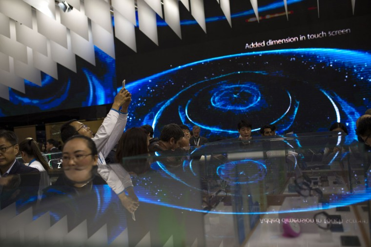 People look at smart phones and other devices displayed at the Chinese ZTE stand during the Mobile World Congress Wireless show in Barcelona, Spain, Tuesday, Feb. 23, 2016. (AP Photo/Francisco Seco)