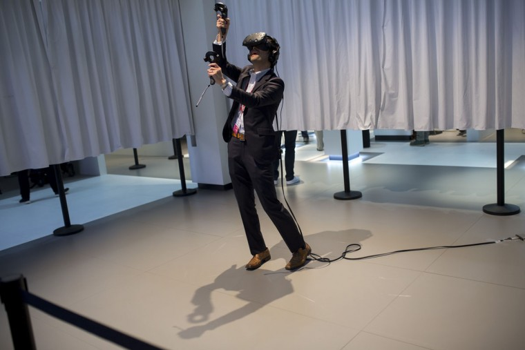 A man uses HTC virtual reality gadgets to play a game during the Mobile World Congress Wireless show in Barcelona, Spain, Wednesday, Feb. 24, 2016. Companies like Samsung, LG and HTC are showing off their latest virtual reality headsets as others are showing new content or new applications for a virtual reality world which is one of the big trends at the Mobile World Congress show in Barcelona. (AP Photo/Francisco Seco)