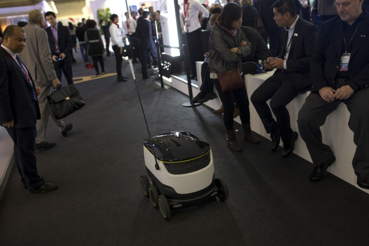 A tub-sized wheeled delivery robot runs among visitors during the Mobile World Congress Wireless show in Barcelona, Spain, Tuesday, Feb. 23, 2016. (AP Photo/Francisco Seco)