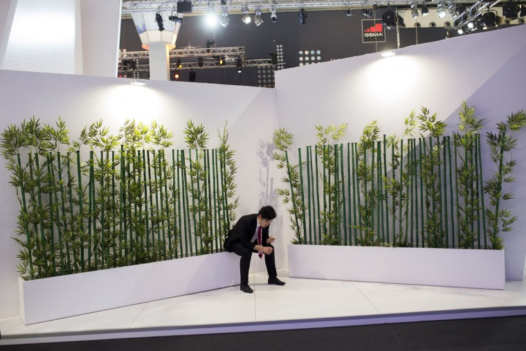 A man looks at his phone during the Mobile World Congress Wireless show in Barcelona, Spain, Tuesday, Feb. 23, 2016. (AP Photo/Francisco Seco)