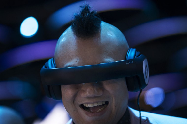 A man smiles as he uses a car racing simulator device during the Mobile World Congress Wireless show in Barcelona, Spain, Tuesday, Feb. 23, 2016. (AP Photo/Francisco Seco)