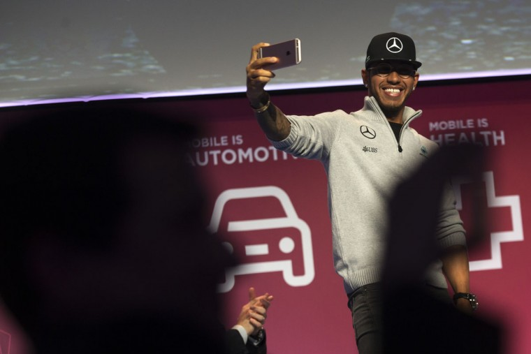 Mercedes driver Lewis Hamilton from Britain takes photographs of the audience with his phone during the Mobile World Congress Wireless show in Barcelona, Spain, Tuesday, Feb. 23, 2016. (AP Photo/Francisco Seco)