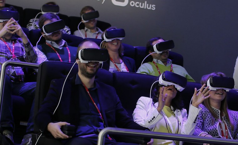 People react as they use the new Samsung Gear 360, a 360-degree camera, at the Mobile World Congress wireless show in Barcelona, Spain, Tuesday, Feb. 23, 2016. (AP Photo/Manu Fernandez)