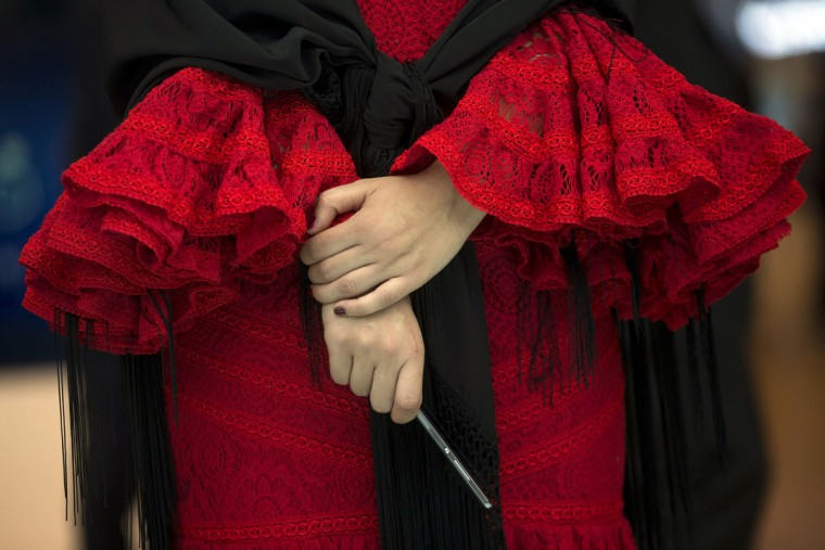 A woman wearing a traditional flamenco costume holds a smartphone during the Mobile World Congress Wireless show in Barcelona, Spain, Wednesday, Feb. 24, 2016. (AP Photo/Francisco Seco)
