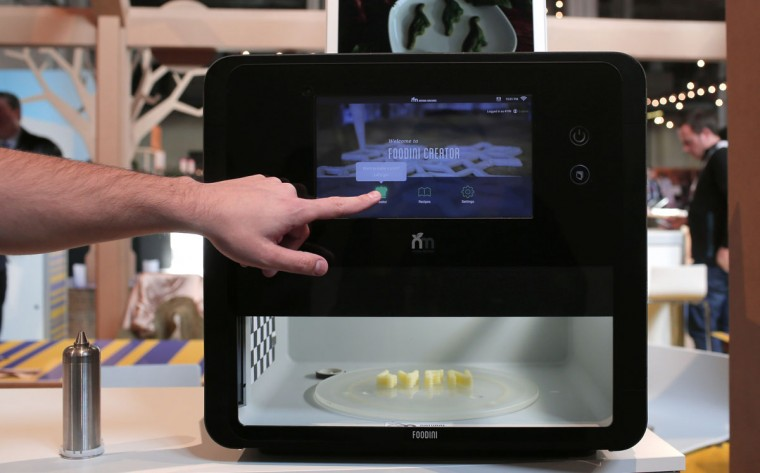 """A man touches the screen of a 3-D food printer during the Mobile World Congress wireless show in Barcelona, Spain, Tuesday, Feb. 23, 2016. Natural Machines co-founder Lynette Kucsma insisted her company hadn't replicated Star Trek's """"food synthesizer"""" that made munchies appear at Captain Kirk's mere command. But they sure have come pretty close with their 3-D food printer. (AP Photo/Manu Fernandez)"""