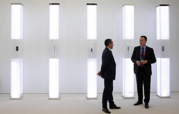 A staff members talks in front of a glass cabinet with a Samsung Galaxy S7, Samsung Galaxy S7 Edge and Samsung Gear 360 camera during the Mobile World Congress wireless show in Barcelona, Spain, Wednesday, Feb. 24, 2016. (AP Photo/Manu Fernandez)