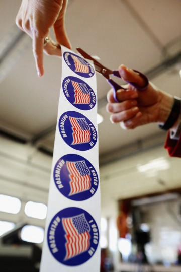 Poll worker Laura Villalba cuts a roll of stickers she will give to voters after they cast their ballots inside the Arlington County Fire Station 10 during Super Tuesday voting March 1, 2016 in Arlington, Virginia. Officials are expecting a record turnout of voters in Virginia, one of a dozen states holding presidential primaries or caucuses. (Chip Somodevilla/Getty Images)