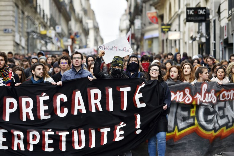 Young people hold a banner as thousands of people demonstrate on March 9, 2016 in Nantes, western France, as part a nationwide day of protest against proposed labour reforms. France faced a wave of protests against deeply unpopular labour reforms that have divided an already-fractured Socialist government and raised hackles in a country accustomed to iron-clad job security. (AFP / Loic Venance)