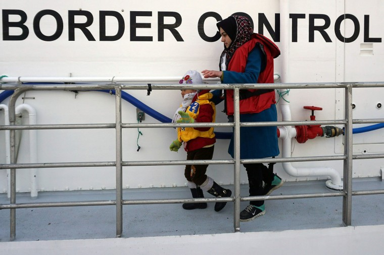 A woman and her child disembarks from a Norwegian Frontex vessel at the port of Mytilene in the island of Lesbos , on March 16, 2016. The Nowergian vessel saved some 250 refugees and migrants who attempted the perilous crossing from Turkey to the Greek island on Lesbos European leaders scrambled Wednesday to salvage an under-fire deal with Turkey to ease the migrant crisis with a round of shuttle diplomacy on the eve of a crunch summit. (STR/AFP/Getty Images)