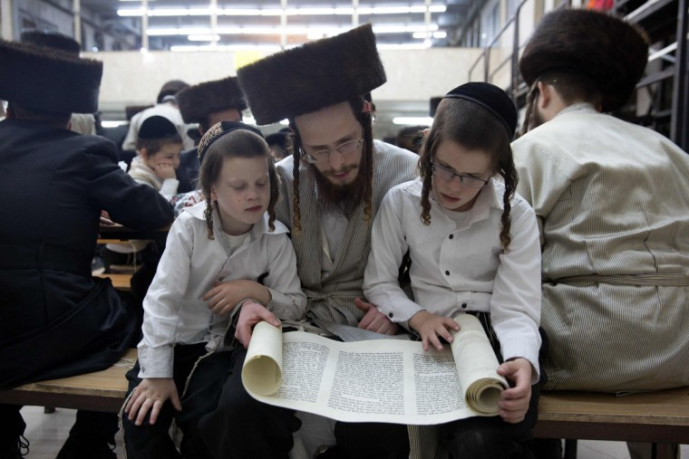An Ultra-Orthodox Jew and his children read the book of Esther at a synagogue in the Israeli city of Beit Shemesh on March 23, 2016 during the feast of Purim. The carnival-like Purim holiday is celebrated with parades and costume parties to commemorate the deliverance of the Jewish people from a plot to exterminate them in the ancient Persian empire 2,500 years ago, as recorded in the Biblical Book of Esther. (AFP Photo/Menahem Kahana)