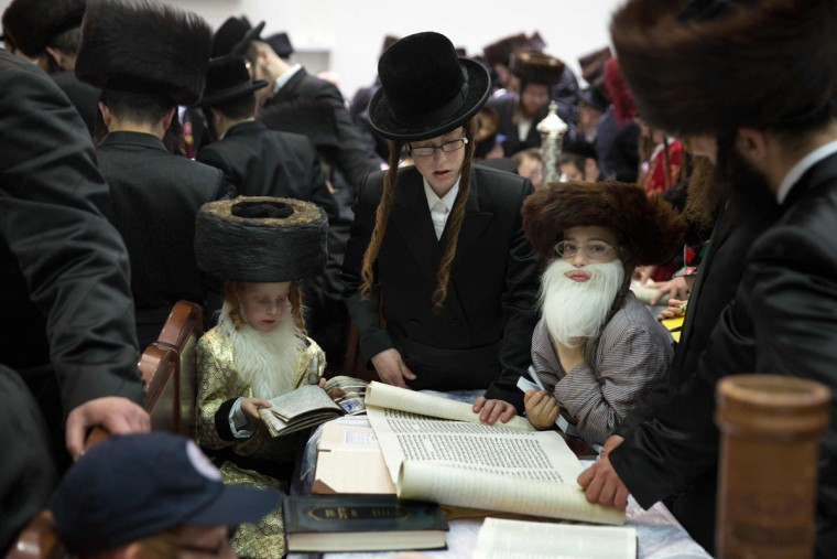 Ultra-Orthodox Jews and dressed up children read the book of Esther at a synagogue in the Israeli city of Beit Shemesh on March 23, 2016 during the feast of Purim. The carnival-like Purim holiday is celebrated with parades and costume parties to commemorate the deliverance of the Jewish people from a plot to exterminate them in the ancient Persian empire 2,500 years ago, as recorded in the Biblical Book of Esther. (AFP Photo/Menahem Kahana)