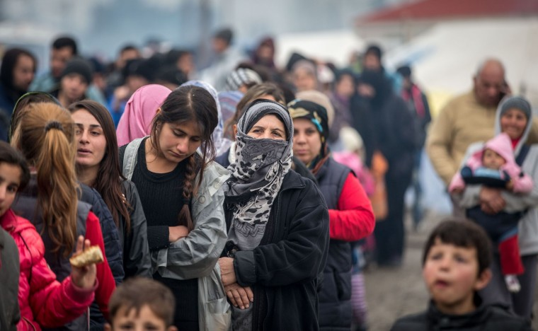 People wait for food aid at the Idomeni refugee camp on the Greek Macedonia border on March 16, 2016 in Idomeni, Greece. The decision by Macedonia to close its border to migrants last week has left thousands of people stranded at the Greek transit camp. The closure, following the lead taken by neighbouring countries, has effectively sealed the so-called western Balkan route, the main migration route that has been used by hundreds of thousands of migrants to reach countries in western Europe such as Germany. Humanitarian workers have described the conditions at the camp as desperate, which has been made much worse by recent spells of heavy rain. (Photo by Matt Cardy/Getty Images)