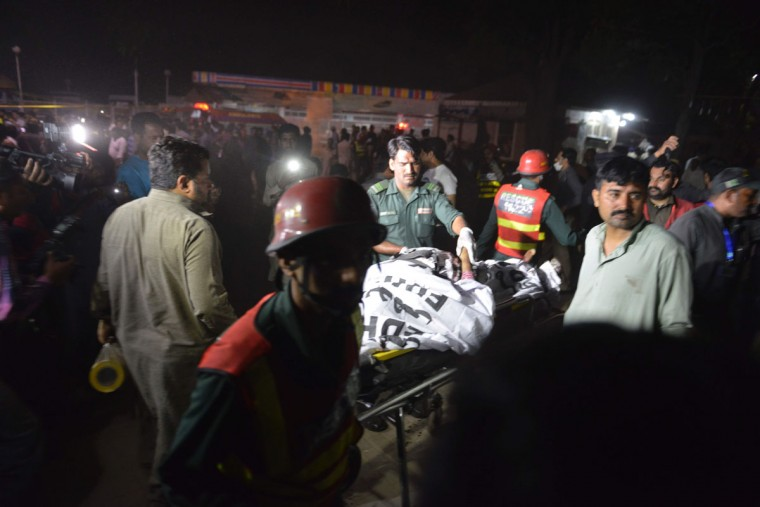 Pakistani rescuers use a stretcher to shift a body from a bomb blast site in Lahore on March 27, 2016. At least 25 people were killed and dozens injured when an explosion ripped through the parking lot of a crowded park where many minority Christians had gone to celebrate Easter Sunday in the Pakistani city Lahore, officials said. (AFP PHOTO / ARIF ALI)