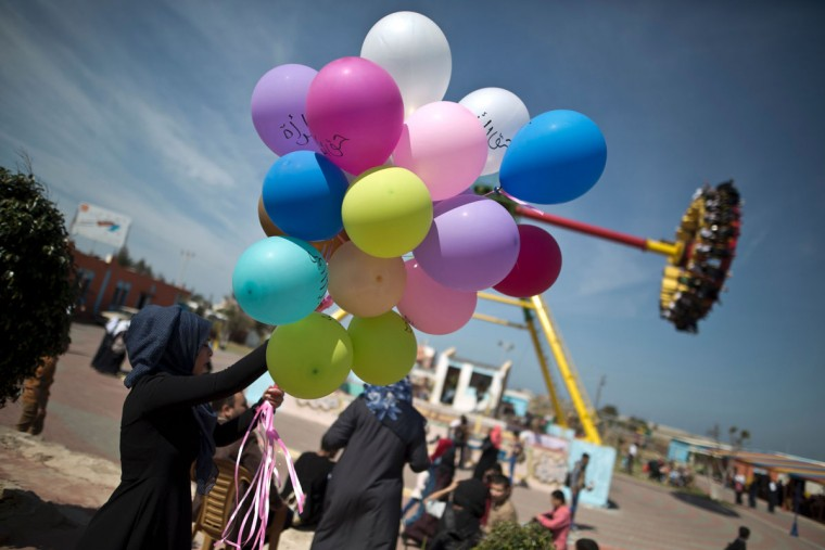 "A Palestinian woman holds balloons, some reading in Arabic ""women's rights"", during an event organized by the United Nations to mark the international women's day on March 8, 2016 at a park in Gaza City. (Mahmud Hams/AFP/Getty Images)"