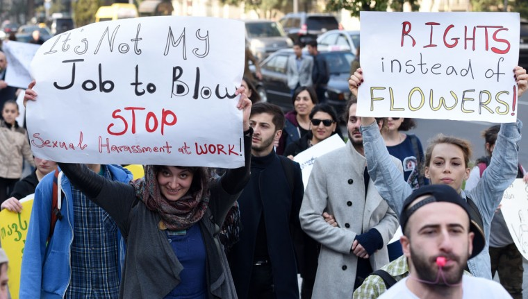 "People hold placards reading ""Rights instead of flowers"" ""It's not my job to blow, stop sexual harassment at work"" during a march celebrating the International Women's Day in Tbilisi, Georgia, on March 8, 2016. (Vano Shlamov/AFP/Getty Images)"