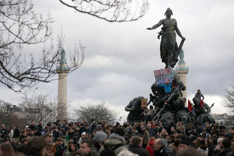 "Jean-Baptiste Redde (R), aka Voltuan, holds a palcard reading ""El Khomri soap opera, uglier the life"" as people gather during a demonstration on the Place de la Republique in Paris, on March 9, 2016, as part a nationwide day of protest against proposed labour reforms. France faced a wave of protests against deeply unpopular labour reforms that have divided an already-fractured Socialist government and raised hackles in a country accustomed to iron-clad job security. (AFP Photo / Thomas Samson)"