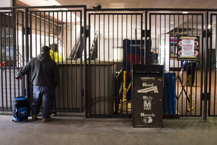 A commuter stands outside the locked gates of the New Carrollton Metro Station in New Carrollton, Maryland on March 16, 2016, after the DC Metro system closed for 24 hours for maintenance. Washington's Metro train system is shut down all day for emergency inspections after an electrical fire in a tunnel, transport chiefs said, in an unprecedented move that threatens to cause mass disruption in the US capital. (AFP Photo / Jim Watson)