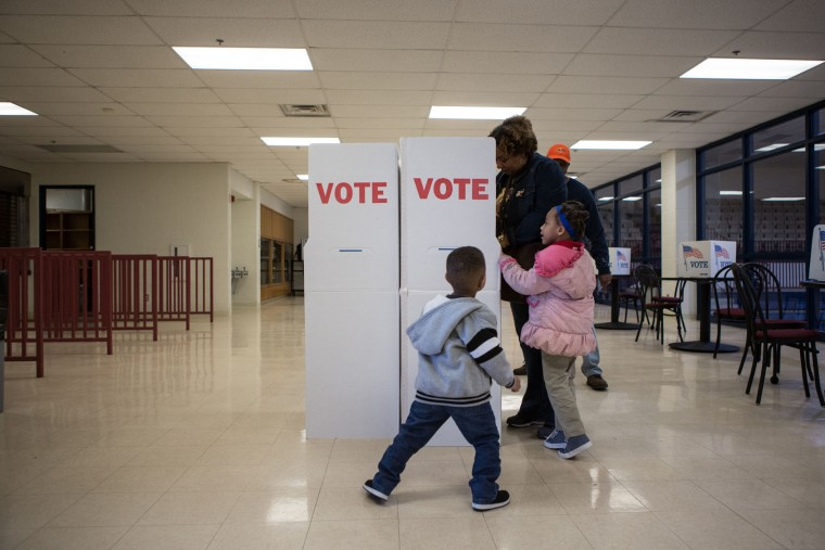 Children play as their grandmother votes at Millwood High School on Super Tuesday March 1, 2016 in Oklahoma City. Oklahoma voters head to the polls for the 2016 Presidential Primary. (Photo by Brett Deering/Getty Images)