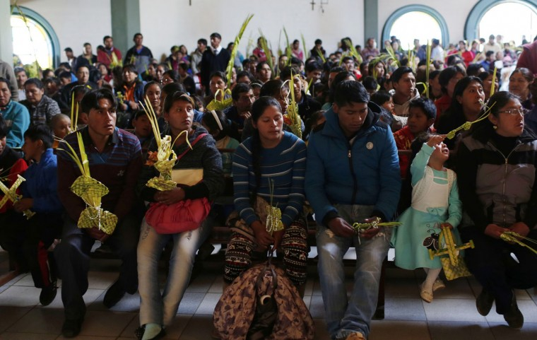 People holds palm fronds during Palm Sunday Mass inside a church in El Alto, Bolivia, Sunday March 20, 2016. For Christians, Palm Sunday marks Jesus Christ's entrance into Jerusalem, when his followers laid palm branches in his path, prior to his crucifixion. (AP Photo/Juan Karita)