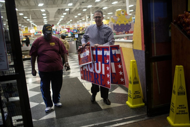 Volunteer election clerks Allie Green Jr., left, and Paul Tryhus, right, briefly leave a Fiesta Mart supermarket, a polling location, to place voting signs, before polls open in Austin, Texas on Tuesday, March 1, 2016. Republicans will vote in 11 states, with 595 delegates at stake. Democrats will vote in 11 states and American Samoa, with 865 delegates up for grabs. Some states have contests Tuesday for only one party. (AP Photo/Tamir Kalifa)