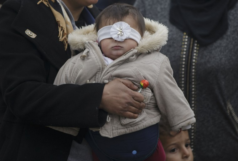 A woman holds a little girl who's head band covers her eyes at the northern Greek border point of Idomeni, Greece, Wednesday, March 16, 2016. Leaders of the EU's 28 divided nations plan to reconvene in Brussels this week in hopes of ironing out disagreements on a proposed agreement with Turkey in the migrants crisis. (AP Photo/Vadim Ghirda)