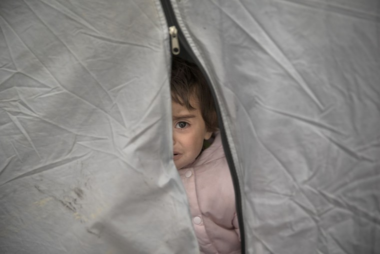 A baby of a migrant family cries in a tent at the northern Greek border point of Idomeni, Greece, Wednesday, March 16, 2016. Leaders of the EU's 28 divided nations plan to reconvene in Brussels this week in hopes of ironing out disagreements on a proposed agreement with Turkey in the migrants crisis. (AP Photo/Vadim Ghirda)